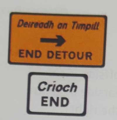 Sinais de trânsito incluindo faixa de pedestre em inglês end-detour