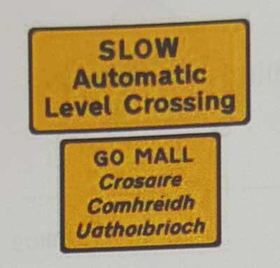 Sinais de trânsito incluindo faixa de pedestre em inglês level-crossing