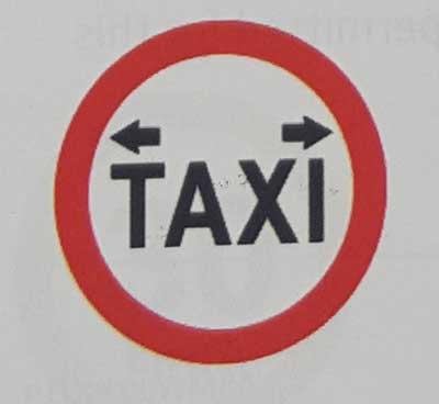 Sinais de trânsito incluindo faixa de pedestre em inglês taxi